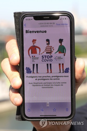 In this file photo taken on May 29 shows the French junior minister for the digital economy holding a mobile phone as he presents the StopCovid contact tracing app at the Ministry of Economy in Paris. [AFP/YONHAP]