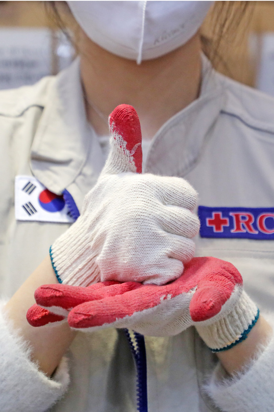 "A Red Cross volunteer in Suwon, Gyeonggi, signs the Korean sign language word for 'respect"" or 'pride"" on April 28, 100 days after Korea's first Covid-19 case.[NEWS1]"