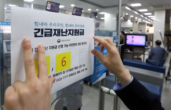 An employee posts a notice informing the public to apply for emergency government reliefs at Shinhan Bank in Jung-district, central Seoul, on May 18. [YONHAP]