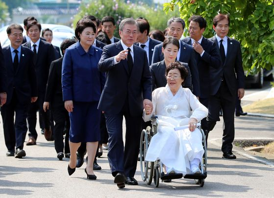 President Moon Jae-in escorts Lee Yong-soo, a survivor of Japanese wartime sexual slavery, to an event aimed to commemorate the pain and suffering of those victims in a national cemetery on Aug. 14, 2018. [JOINT CORPS]