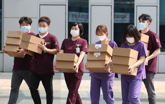 Medical professionals at the Seoul Medical Center head back to work after receiving gift boxes full of food on Tuesday. The Seoul Bus Association sent boxes of food bought from traditional markets to thank medical professionals working in the hot weather on the front lines of the fight against the coronavirus pandemic. [YONHAP]