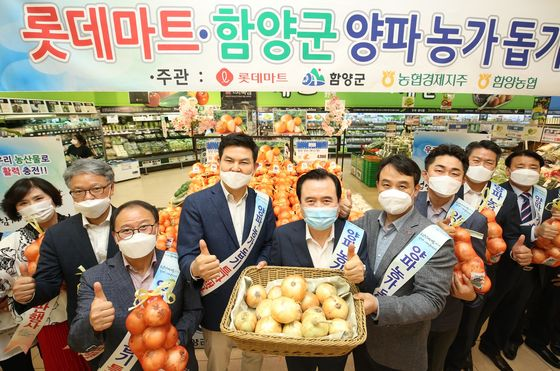 Officials from Lotte Mart and Hamyang County in South Gyeongsang, including county Mayor Seo Chun-soo, fifth from right, promote onions at Lotte Mart's Seoul Station branch in central Seoul. [LOTTE SHOPPING]