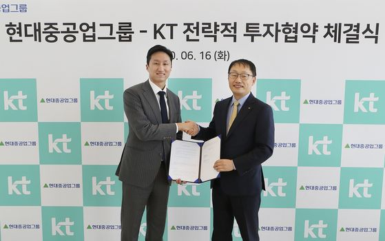 Hyundai Heavy Industries Senior Vice President Chung Ki-sun, left, and KT CEO Koo Hyun-mo pose at the signing of KT's pre-IPO stock acquisition deal in Hyundai Robotics, Tuesday, at the mobile carrier's office in central Seoul. [KT, HYUNDAI HEAVY INDUSTRIES]
