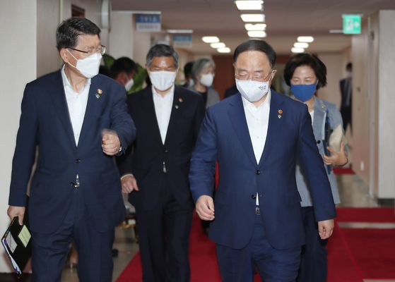 Finance Minister Hong Nam-ki, right, heads to a meeting of ministers at the government complex in Seoul on Tuesday. [YONHAP]