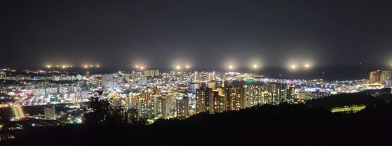 Fishing boats shine powerful lights to catch squid off the coast of Sokcho, Gangwon, Monday night. [YONHAP]