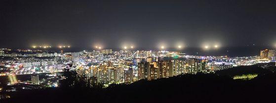 Fishing boats shine powerful lights to catch squid off the coast of Sokcho, Gangwon, Monday night. [YONHAP]