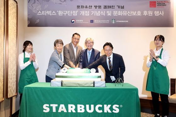 From left: Chung Jae-suk, administrator of the Cultural Heritage Administration and Song Ho-seob, CEO of Starbucks Korea, pose with other officials at the reopening event for Starbucks' Hwangudan store in Jung District, central Seoul. [YONHAP]