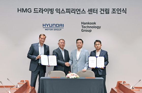 Euisun Chung, executive vice chairman at Hyundai Motor Group, second from left, shakes hands with Cho Hyun-sik, vice chairman at Hankook Technology Group, after signing a partnership on the establishment of HMG Driving Experience Center at the automaker's Yangjae headquarters in southern Seoul on June 17. [HYUNDAI MOTOR GROUP]