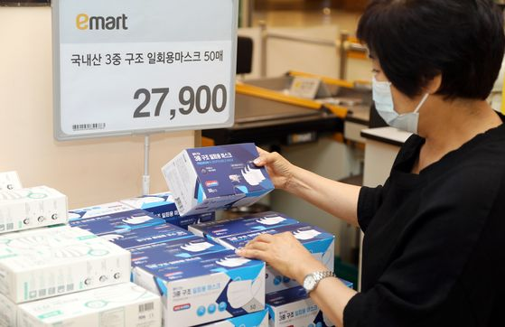 A customer looks at a box of disposable face masks made in Korea at an Emart store. [EMART]