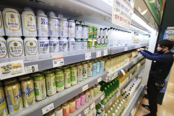 An employee organizes cans of non-alcoholic beer on a shelf at a discount store in Seoul on Thursday. As more Koreans prefer to drink responsibly, competition for non-alcoholic beer is heating up. Hite Jinro was the first to enter the market, followed by Chinese Tsingtao, which launched a low-alcohol beer on June 11. Market leader Oriental Brewery Company said it plans to launch a non-alcoholic beer this year. [YONHAP]