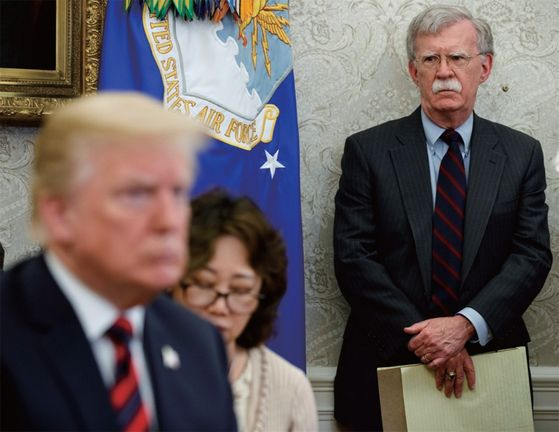 Former White House National Security Adviser John Bolton, right, looks at U.S. President Donald Trump, left, during a summit with South Korean President Moon Jae-in last year. [AP/YONHAP]