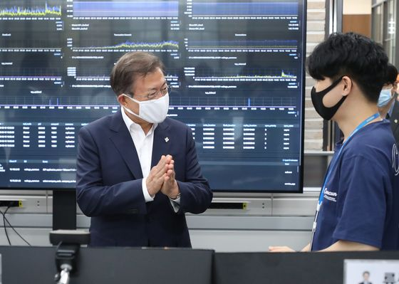 President Moon Jae-in, left, talks with an employee of Douzone, a data platform company, at its office in Chuncheon, Gangwon, on Thursday.  [YONHAP]