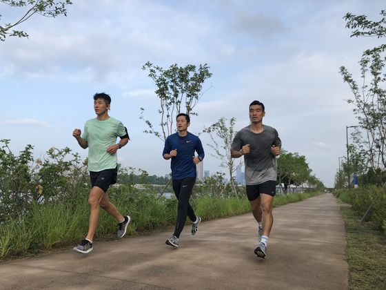 Sean, left, and Lee Young-pyo, center, both goodwill ambassadors of Compassion Korea, during a run. [YG ENTERTAINMENT]
