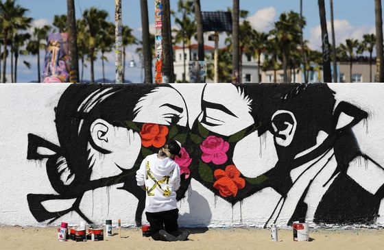 Artist Pony Wave paints a scene depicting two people kissing while wearing face masks on Venice Beach on March 21 in Venice, California. [AFP/YONHAP]
