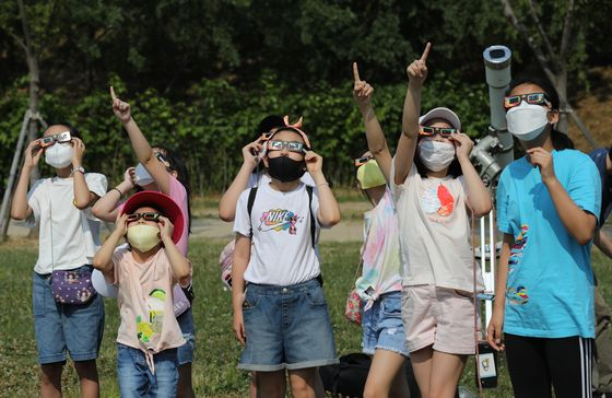 At a park on the bank of the Han River in Seoul, people observe the largest partial solar eclipse in eight years in Korea on Sunday afternoon. The moon moved between the Earth and the Sun at 3:53 p.m., with the transit to end at 6:04 p.m., the Gwacheon National Science Museum said. [NEWS1]
