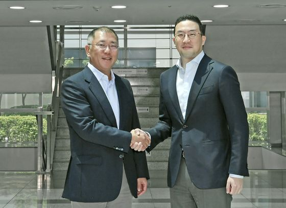 Hyundai Motor Group Executive Vice Chairman Euisun Chung, left, shakes hands with LG Group Chairman Koo Kwang-mo on Monday at LG Chem's battery factory in Ochang, North Chungcheong. [HYUNDAI MOTOR GROUP]