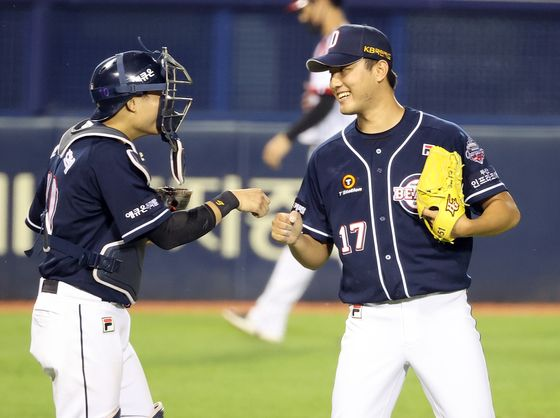 The Doosan Bears pitcher Hong Geon-hui and cacher Park Sei-hyok celebrate after the Bears picked up their third win against the LG Twins at Jamsil Baseball Stadium in southern Seoul on Sunday. [ILGAN SPORTS]