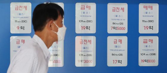 Apartment sales posted in front of a real estate agency in Jamsil on Monday. Calls have been ringing off the hook as home buyers are trying to purchase the apartment before the tougher government regulations go into effect. [YONHAP]