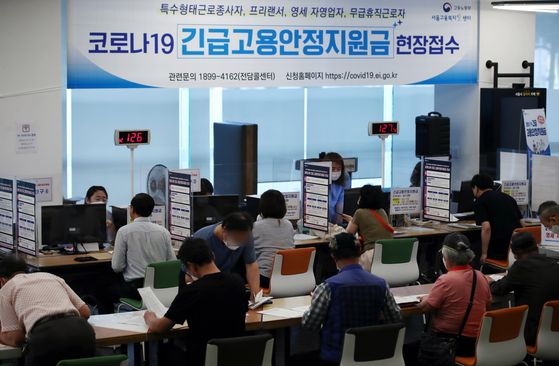 Applicants apply for the government's emergency relief fund at a welfare support center in Jung District, central Seoul, on Monday. Starting Monday, people hit hard by the coronavirus pandemic are entitled to apply for a subsidy of 1.5 million won ($1,200). Applications are open until July 3. [YONHAP]
