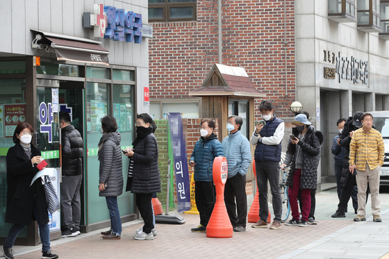 People line up in front of a drug store in Jongno District, central Seoul, to receive publicly-distributed masks on March 21. The national health insurance database was used in limiting the masks to two per person every week as there was a surge in demand after the number of coronavirus cases shot up after many Shincheonji members especially in Daegu contracted the virus, forcing the city to lock down. [YONHAP]