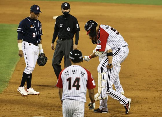 Chae Eun-seong of the LG Twins, right, is carried off the field by a team training after spraining his right ankle during a game against the Doosan Bears at Jamsil Baseball Stadium in Seoul on June 21. [NEWS1]