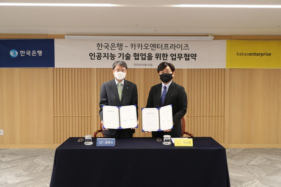 Yoon Myun-shik, the Bank of Korea's senior deputy governor, left, and Baek Sang-yeop, CEO of Kakao Enterprise pose for a photo after signing an MOU on Tuesday at the bank's headquarters in Jung District, central Seoul. [BANK OF KOREA]