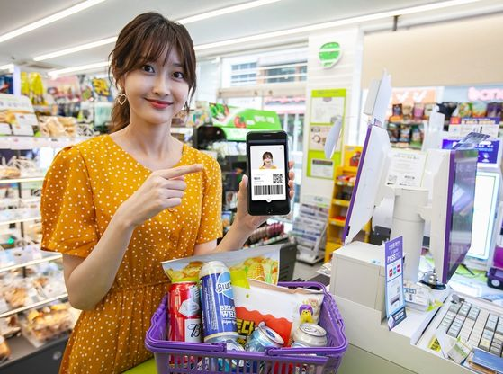 A model buys beer using a digital driving license on the PASS app at a CU convenience store. [BGF RETAIL]