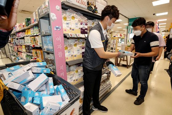 An Emart employee hands out a box of anti-droplet facial masks to a customer at the retailer's branch in Seongsu-dong, eastern Seoul, on Wednesday. The anti-droplet masks are said to be lighter than the KF94 masks, making it easier to breathe. Each customer is limited to 20 masks, which cost 500 won ($0.42) a piece. [YONHAP]