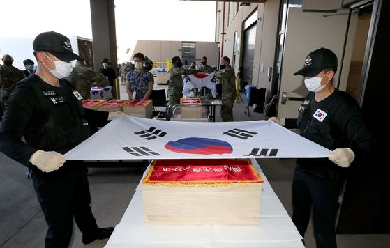 South Korean soldiers hold the country's national flag over a box containing the remains of fallen soldiers from the Korean War returned to the South on Wednesday. [NEWS1]