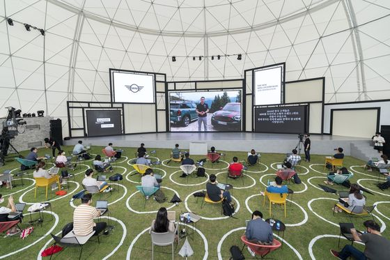 Bernd Korber, head of MINI, speaks through a screen at the world premiere of the new MINI Countryman in Yongin, Gyeonggi on Wednesday. The event was held at a campsite and followed Korea's social distancing policies, with reporters sitting apart from each other amid the outbreak of the coronavirus. [BMW KOREA]