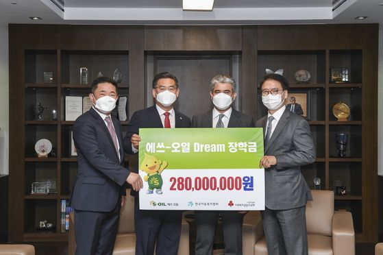 S-Oil CEO Hussain Al-Qahtani, third from left, holds a banner celebrating the donation on Wednesday at the company's headquarters in Mapo District, western Seoul. [S-OIL]