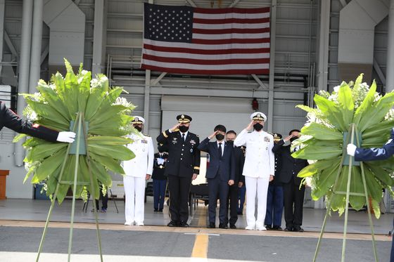 South Korean and U.S. defense and military officials salute the remains of fallen South Korean troops handed off to Seoul in a ceremony at Hawaii on Wednesday. [MINISTRY OF NATIONAL DEFENSE]
