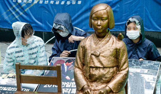 "University students tie themselves to a statue symbolizing 'comfort women"" victims in front of the old Japanese Embassy in central Seoul Wednesday and stage a sit-in protest after the organizers of weekly rallies to resolve the issue of Japanese wartime sexual slavery lost their usual turf to a conservative group. [NEWS1]"