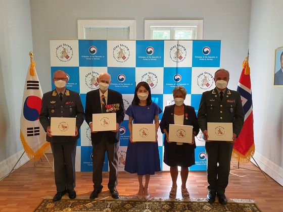 Nils Steen Egelien, president of the Norwegian Korean War Veterans Association, second from left, and Korean Ambassador to Norway Nam Young-sook pose during a ceremony to present the masks to Korean War veterans at the embassy in Oslo on June 15. [EMBASSY OF KOREA IN NORWAY]