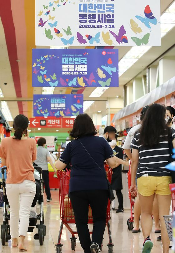 Customers shop at a discount store Thursday, a day before the start of the summer blowout sale that runs from Friday to July 15, which was planned by the government to help Korean retailers make up for the losses from the coronavirus pandemic during the first half of the year. Major retailers have been distributing discount coupons a day before the event. [YONHAP]