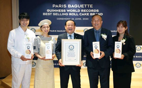 Paris Croissant CEO Hwang Jae-bok, center, holds a Guinness World Records certificate for Paris Baguette's bestselling Silky Roll Cake. More than 12 million cakes were sold between January 2015 and December 2019 in five nations - Korea, China, the United States, Singapore and Vietnam. [PARIS BAGUETTE]