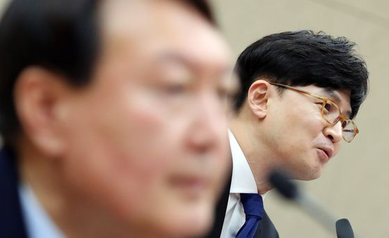 In this file photo, Han Dong-hoon, a senior prosecutor and a close associate of Prosecutor General Yoon Seok-youl, right, speaks during an Oct. 17 National Assembly hearing. Yoon, left, also attended the session. The Ministry of Justice said it will directly investigate Han for alleged collusion with a reporter.  [YONHAP]