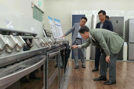 Samsung Electronics Vice Chairman Lee Jae-yong, front, checks a kitchen appliance on Tuesday during a visit to the company's home appliance factory in Suwon, Gyeonggi. [YONHAP]