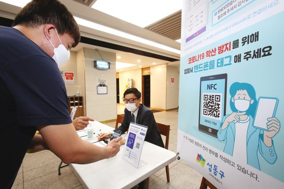 A visitor to Hanyang University Seoul Hospital in Seongdong District, central Seoul, scans a QR code Friday before entering a funeral hall. The Korean government earlier this month mandated places with a high risk of Covid-19 transmission to adopt a QR code system to digitally register visitors' identities. [YONHAP]