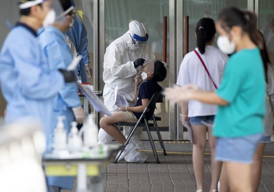 Students get tested for Covid-19 at a center set up at Nanwoo Elementary School in Gwanak District, southern Seoul, on Sunday, after a lecturer at the school was diagnosed with the coronavirus. [YONHAP]