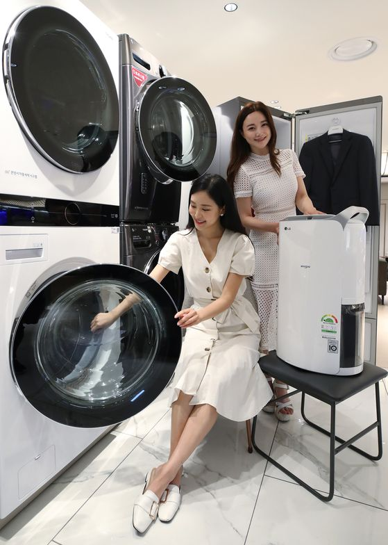 Models show off home appliances at an LG Electronics store in Lotte Department Store headquarters in Jung District, central Seoul, on Monday. The household appliances are especially popular during the hot, rainy season. [YONHAP]