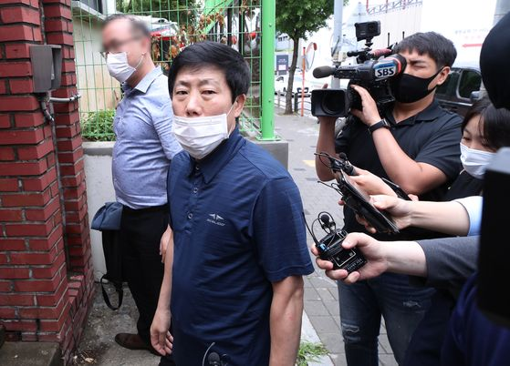 Park Sang-hak, head of Fighters for a Free North Korea, looks at the press before stepping into police offices in western Seoul for questioning on Tuesday. [YONHAP]