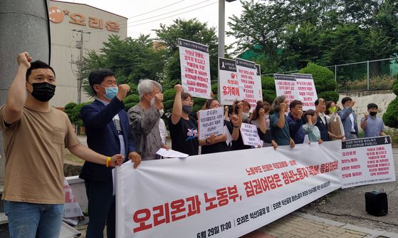 A group of people rally against workplace bullying in front of the Orion factory in Iksan, North Jeolla, on Monday. The group held a press event demanding Orion apologize to the bereaved and arrange measures to prevent similar incidents in the future. [YONHAP]