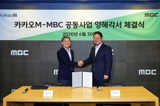 CEO of Kakao M, Kim Sung-soo, left, and MBC CEO Park Sung-jae pose for a photo after signing a memorandum of understanding at the MBC building in Samang-dong, western Seoul, on Tuesday.