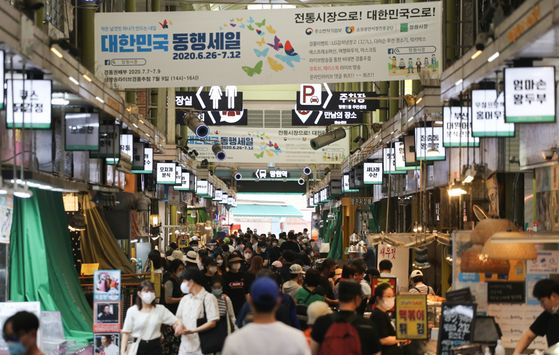 A banner advertising a government-led discount event hangs in the Mangwon Traditional Market in western Seoul on June 28. The government hopes to continue to boost the domestic economy by encouraging spending. However, industry continues to struggle with the impact of the coronavirus pandemic. [YONHAP]