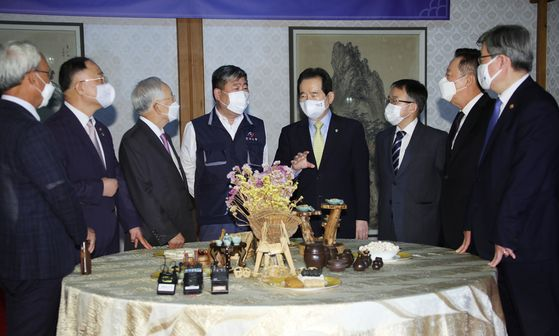 Representatives of the government, labor unions and business management including host Prime Minister Chung Sye-kyun, fourth from right, converse at the prime minster's residence in Seoul on Wednesday ahead of a signing ceremony on labor cooperation. The ceremony was canceled as one of the umbrella labor unions pulled out at the last minute. [YONHAP]