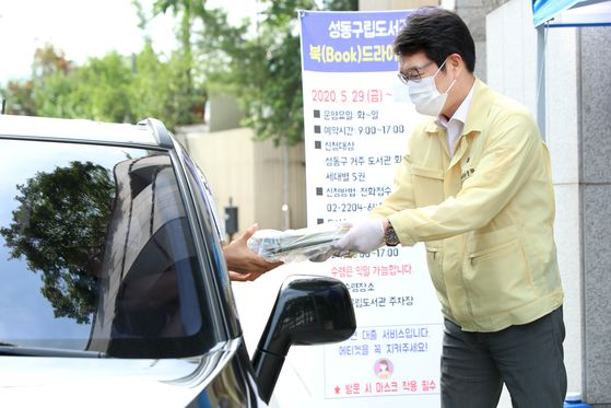Seongdong District Mayor Chong Won-oh hands out books to a driver outside a public library on Wednesday afternoon. The library started providing the drive-through service as a solution for the closure of libraries amid the coronavirus pandemic. [YONHAP]