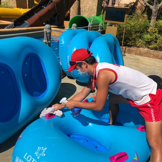 An employee of Lotte Water Park sanitizes a tube for water slides prior to its operation. [LOTTE WATER PARK]