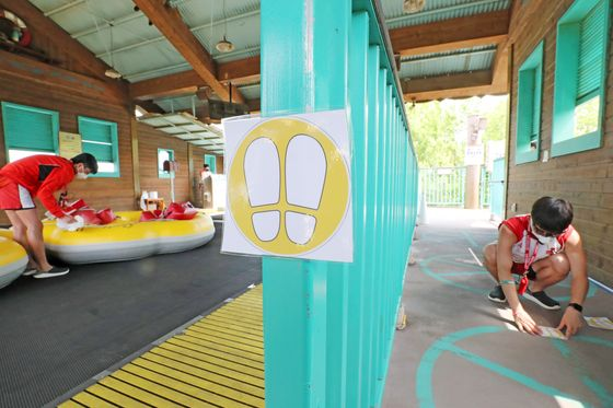 Caribbean Bay employees place stickers on the ground to ensure those lining up for rides maintain social distancing measures. The water park used to have a daily limit of 20,000 visitors but has drastically dropped that threshold to just 1,200. [NEWS1]