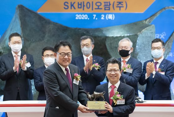 SK Biopharmaceuticals CEO Cho Jeong-woo, left, and Jung Ji-won, CEO and chairman of Korea Exchange pose for a photo holding a memorial tablet celebrating the company's public listing on July 2 at the exchange's headquarters in Yeouido, western Seoul. [YONHAP]